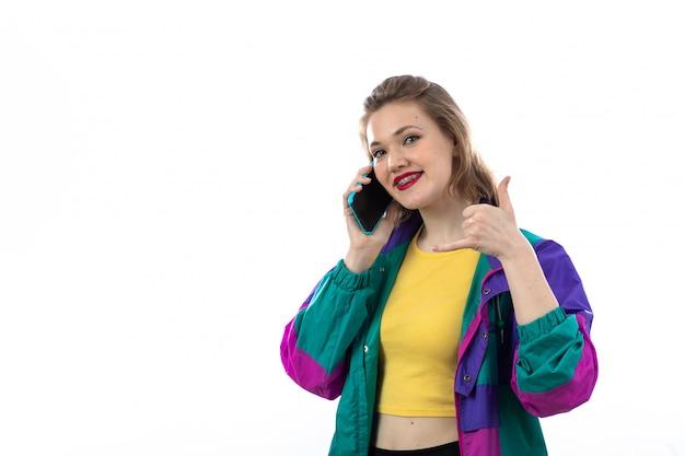 Mooie jonge vrouw in kleurrijke jas met behulp van smartphone