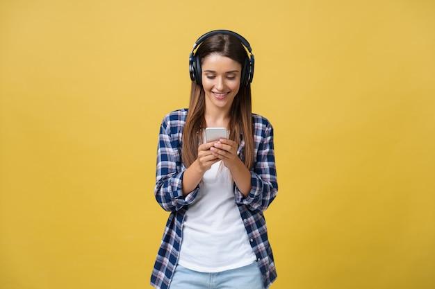 Mooie jonge vrouw in koptelefoon luisteren naar muziek en zingen op gele achtergrond.