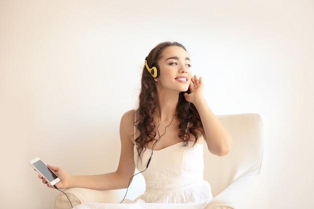 Mooie jonge vrouw in koptelefoon luisteren naar muziek thuis