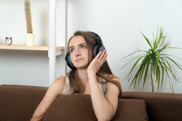 Mooie jonge vrouw in koptelefoon luistert zorgvuldig naar muziek.