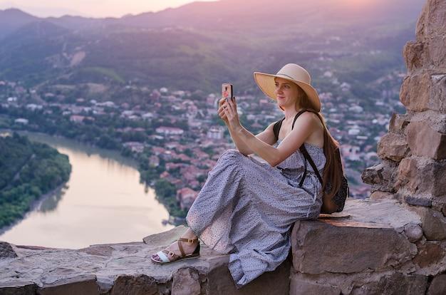 Mooie jonge vrouw in lange jurk en hoed, zit op een heuvel en fotografeert het landschap op de telefoon.