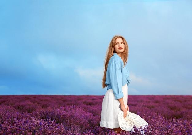 Mooie jonge vrouw in lavendel veld op zomerdag