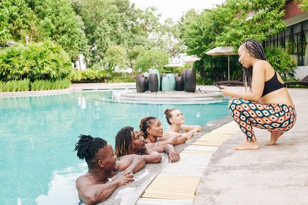 Mooie jonge vrouw in leggings en sport-bh praten met vrienden ontspannen in het zwembad van het kuuroord