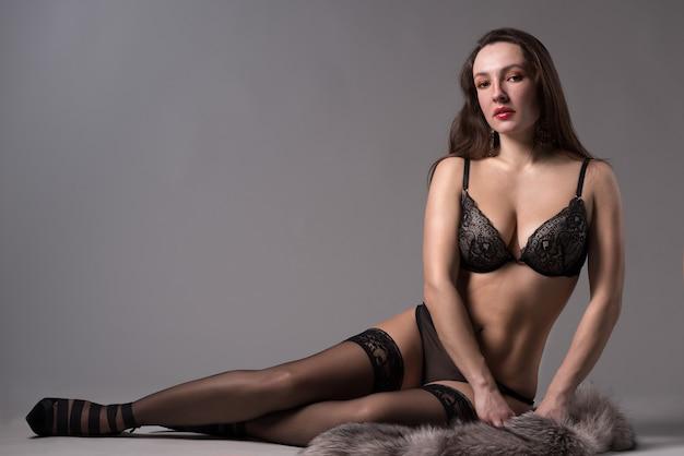 Mooie jonge vrouw in lingerie en bont zit op de vloer op een grijze achtergrond in de studio.