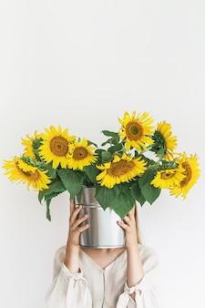 Mooie jonge vrouw in linnen jurk houdt zonnebloemen boeket in een tinnen emmer op witte achtergrond.