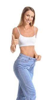 Mooie jonge vrouw in losse jeans met thumb-up op witte ruimte. gewichtsverlies concept