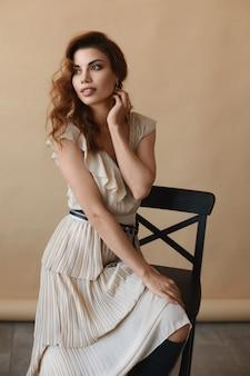 Mooie jonge vrouw in modieuze outfit zit op de kruk en poseren in het interieur.