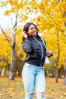 Mooie jonge vrouw in modieuze vrijetijdskleding met een jas, spijkerbroek en een handtas loopt in een herfstpark met gekleurd gouden blad