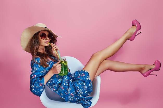 Mooie jonge vrouw in mooie blauwe bloemenprint lente jurk en strooien hoed in een studio mode lente zomer foto emoties roze achtergrond