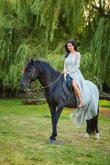 Mooie jonge vrouw in mooie kleding op zwart paard in de natuur
