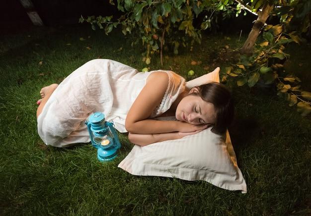 Mooie jonge vrouw in nachtjapon slapen op gras in de tuin 's nachts