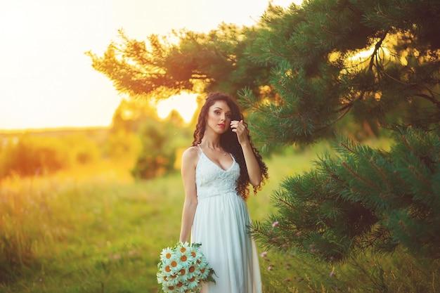 Mooie jonge vrouw in paarse bloemen buitenshuis