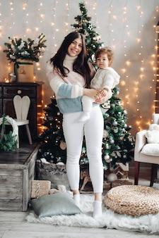 Mooie jonge vrouw in pluizige trui glimlachend terwijl het kind vasthoudt en in de buurt van de kerstboom staat