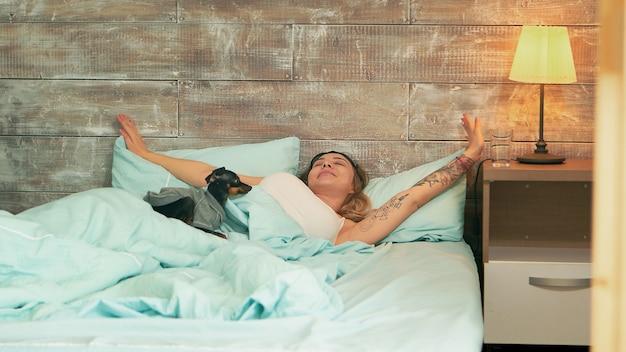 Mooie jonge vrouw in pyjama die haar slaapmasker opstijgt terwijl ze wakker wordt. blije hond.