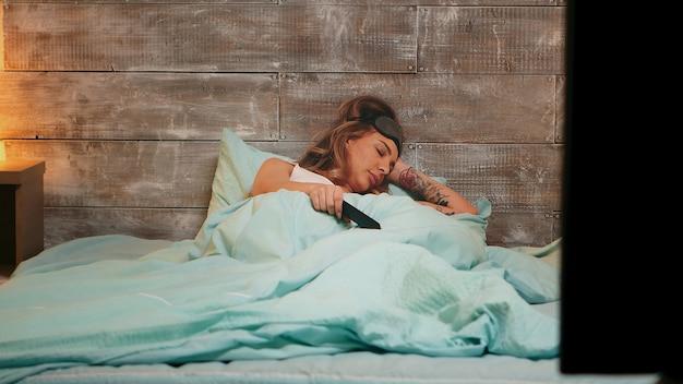 Mooie jonge vrouw in pyjama in slaap vallen tijdens het tv-kijken.
