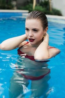 Mooie jonge vrouw in rode bikini verfrissend bij zomerzwembad
