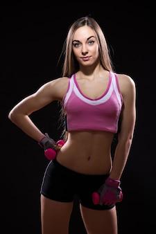 Mooie jonge vrouw in rode bokshandschoenen die over zwarte achtergrond wordt geïsoleerd