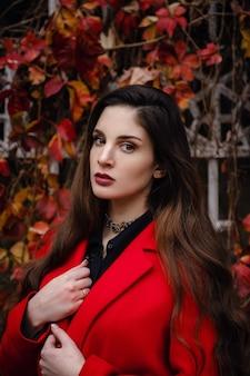 Mooie jonge vrouw in rode jas geniet herfst park