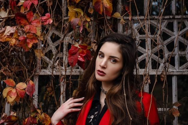 Mooie jonge vrouw in rode jas geniet van herfstpark. een aangename wandeling op de achtergrond van een hek met takken van wilde druiven en rode bladeren