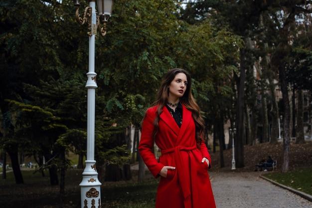 Mooie jonge vrouw in rode jas geniet van herfstpark. een aangename wandeling op de achtergrond van park