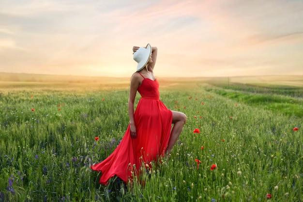 Mooie jonge vrouw in rode jurk en witte hoed loopt rond veld met papavers