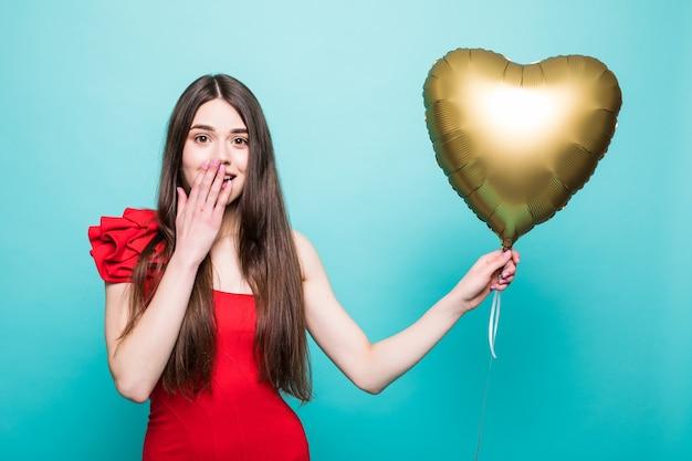 Mooie jonge vrouw in rode jurk met de luchtballon van de hartvorm. vrouw op valentijnsdag. symbool van liefde