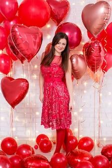 Mooie jonge vrouw in rode jurk met hartvormige ballonnen