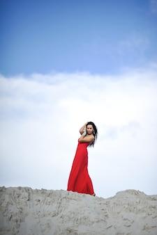 Mooie jonge vrouw in rode jurk op aard achtergrond