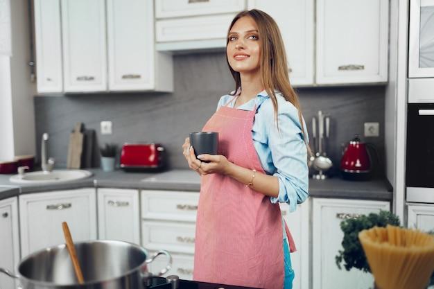 Mooie jonge vrouw in rode schort genieten van een kopje koffie in haar keuken