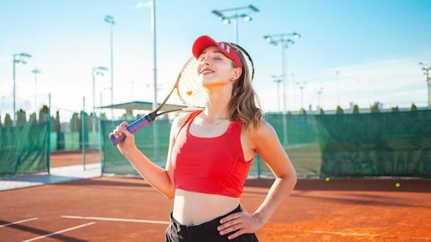 Mooie jonge vrouw in rode sportkleding poseren met tennisracket aan het hof