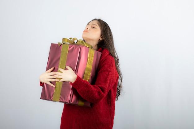 Mooie jonge vrouw in rode trui die staat en een geschenkdoos vasthoudt..