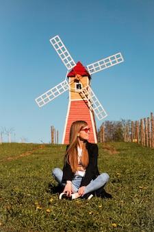Mooie jonge vrouw in rode zonnebril zit op het gras tegen de achtergrond van de rode molen.