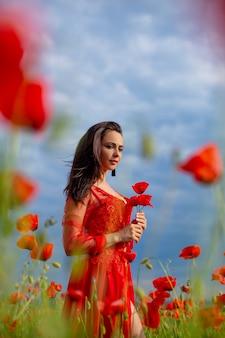 Mooie jonge vrouw in rood in een papavergebied