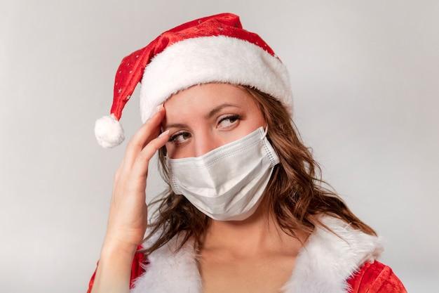 Mooie jonge vrouw in rood kerstmankostuum en beschermend medisch masker tegen virus. concept viert kerstmis in covid 19 pandemie en quarantaine. mevrouw de kerstman ziek covid 19