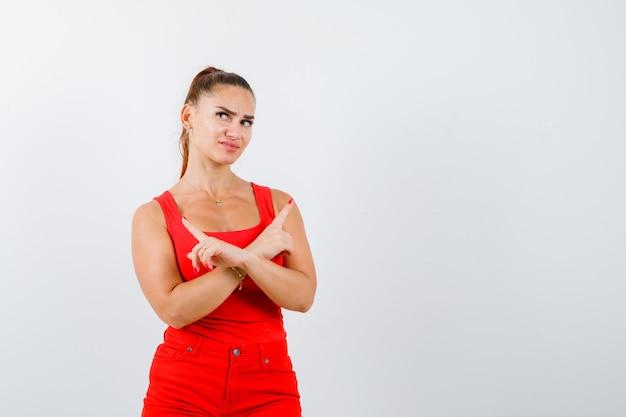 Mooie jonge vrouw in rood mouwloos onderhemd, broek die naar links en rechts wijst en peinzend kijkt, vooraanzicht.