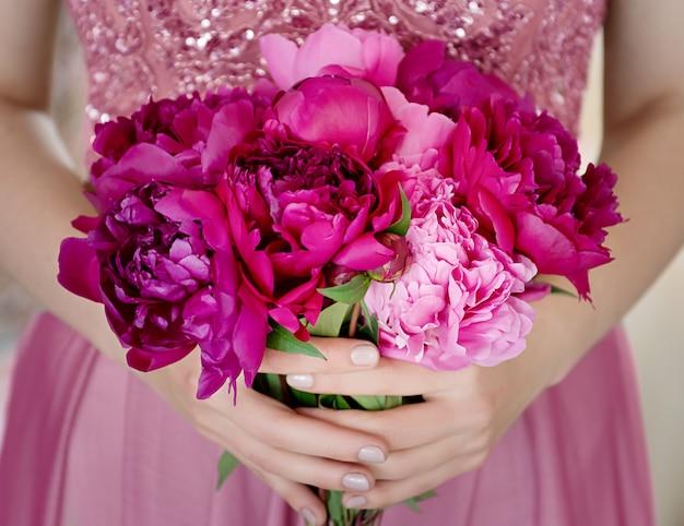 Mooie jonge vrouw in roze jurk met pioenroos bloemen boeket in haar handen