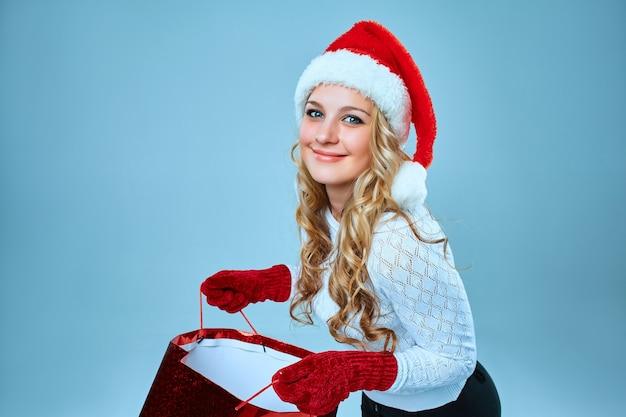 Mooie jonge vrouw in santa claus-kleding met een cadeau op blauw