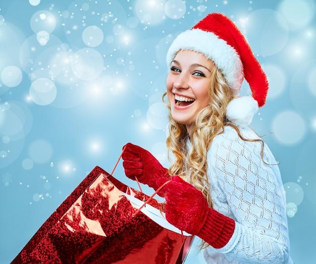 Mooie jonge vrouw in santa claus-kleding met een cadeau op een blauwe achtergrond