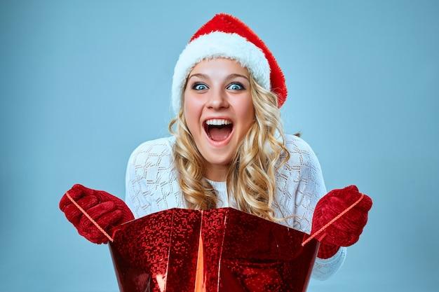 Mooie jonge vrouw in santa claus-kleding met een cadeau op een blauwe achtergrond Premium Foto
