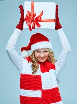 Mooie jonge vrouw in santa claus-kleding met een cadeau op een grijze achtergrond