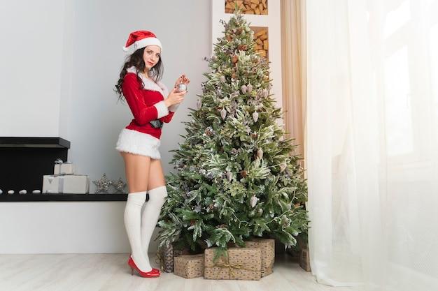 Mooie jonge vrouw in santa claus-kleding siert de kerstboom met speelgoed en ballen. voorbereiding op kerstmis. de inrichting van het appartement. sexy meisje in een verleidelijk pak.