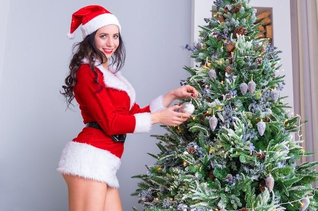 Mooie jonge vrouw in santa claus-kleding siert de kerstboom met speelgoed en ballen. voorbereiding op kerstmis. de inrichting van het appartement. sexy meisje in een verleidelijk pak