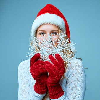 Mooie jonge vrouw in santa claus-kleren met sneeuwvlokken op een blauwe achtergrond