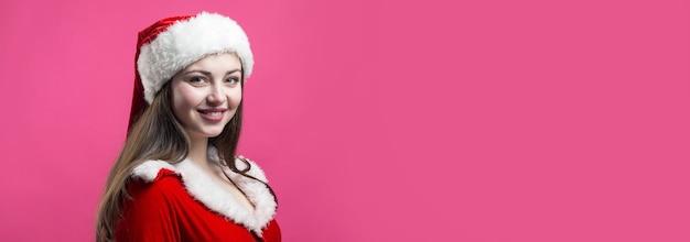 Mooie jonge vrouw in santa claus kostuum tegen de rode achtergrond.