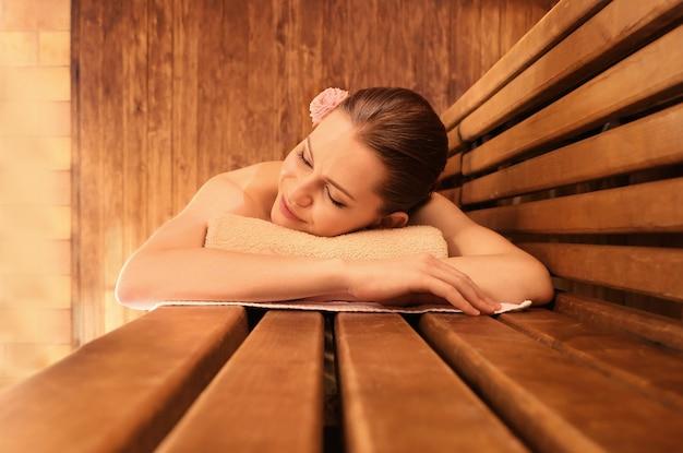 Mooie jonge vrouw in sauna