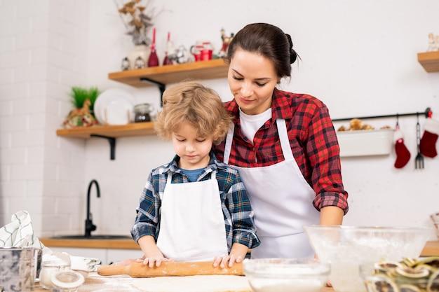Mooie jonge vrouw in schort die zich dicht bij haar zoontje bevindt dat zelfgemaakt deeg voor gebak op lijst rolt
