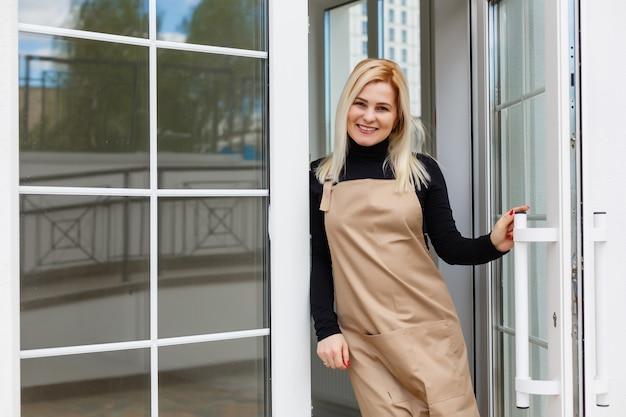 Mooie jonge vrouw in schort en leunend tegen deuropening van het huis van de muurkoffie of restaurant als eigenaar of werknemer