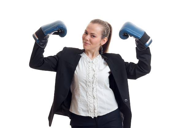 Mooie jonge vrouw in shirt en jas hief haar handen op in bokshandschoenen is geïsoleerd op een witte muur