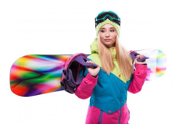 Mooie jonge vrouw in ski-outfit en ski bril houden snowboard