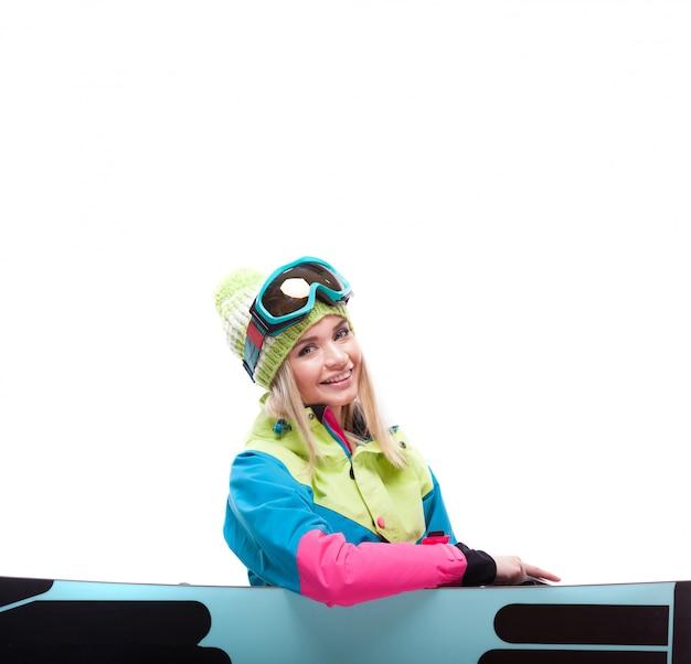 Mooie jonge vrouw in ski-outfit zitten in de buurt van snowboard